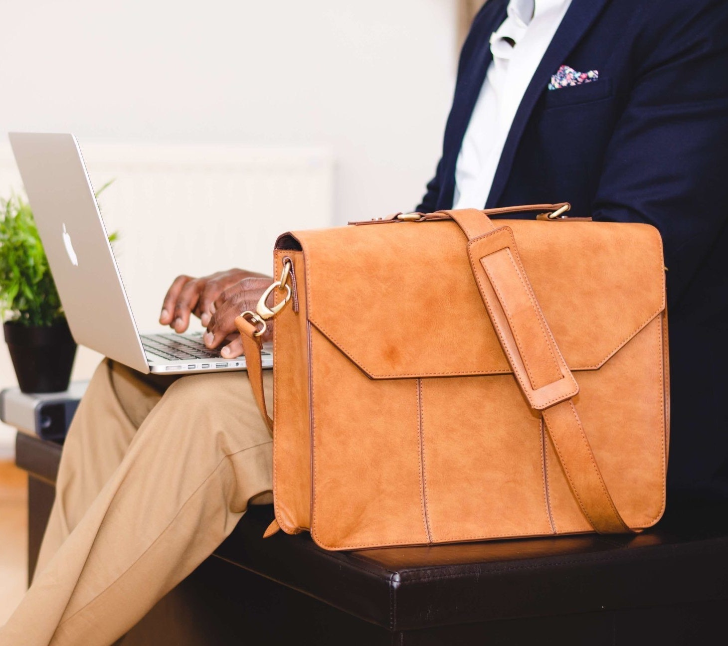 person-wearing-blue-suit-beside-crossbody-bag-and-using-936081